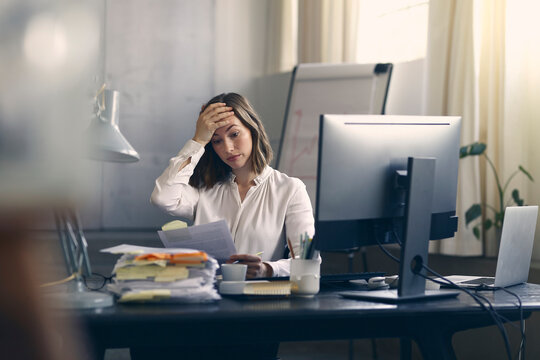 Very stressed business woman sitting in front of her computer looking at a large pile of paperwork, while holding a hand at her forehead