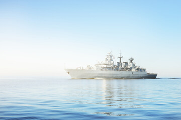 Large grey modern warship sailing in still water. Clear blue sky. Baltic sea, Germany. Global communications, international security theme Fotomurales