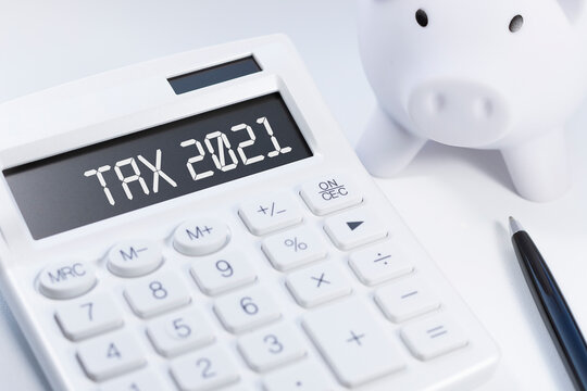 Word Tax 2021 on calculator. Business and tax concept on white background. Top view.