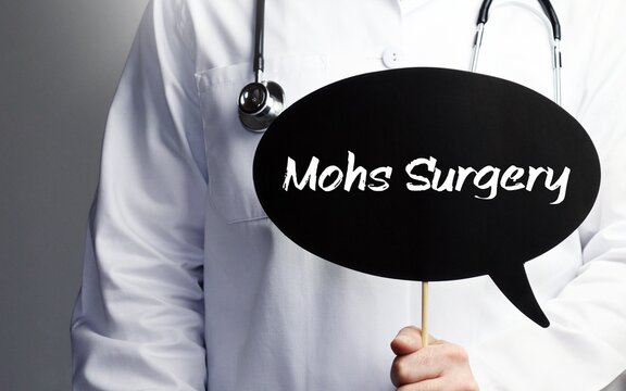 Mohs Surgery. Doctor with stethoscope holds speech bubble in hand. Text is on the sign. Healthcare, medicine