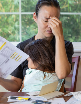 Stressed mother with her child in her lap stressing out about paying utility bills