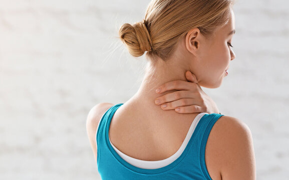 Sports injury. Athletic girl feeling pain in her neck against white background, copy space