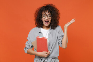 Excited young african american student girl in casual clothes, eyeglasses isolated on orange background studio portrait. People lifestyle concept. Mock up copy space. Hold books, pointing hand aside.