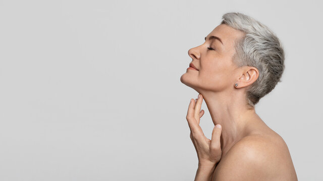 Anti-Age Treatment. Beautiful middle-aged woman touching soft skin on her neck