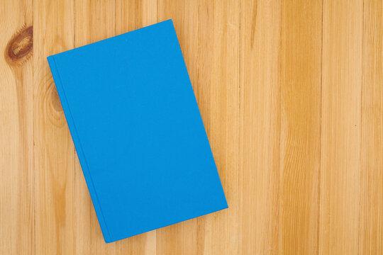 Blue hardcover book on pine wood desk