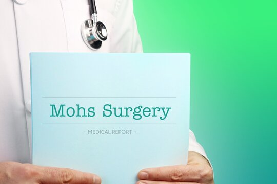 Mohs Surgery. Doctor (male) with stethoscope holds medical report in his hands. Cutout. Green turquoise background. Text is on the documents. Healthcare/Medicine