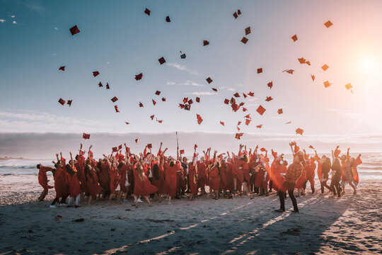 high school of college class of 2020 in a silhouette of people jumping on the beach tossing their caps or hats in the air in celebration of graduation.
