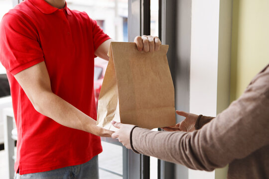 Modern delivery of any order. Girl takes package from hands of courier