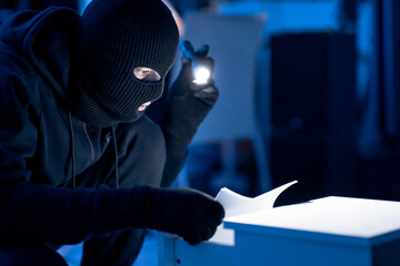 Masked intruder holding and reading confidential documents - fototapety na wymiar