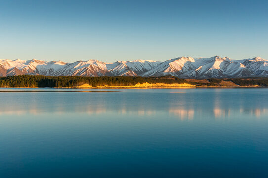 Sunrise winter mountains landscape with calm lake and water reflections