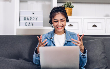 Young smiling happy beautiful asian woman relaxing using laptop computer working and video conference meeting at home.Young creative girl talk with with headset.work from home concept