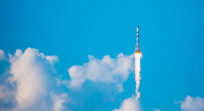 Take-off of a real launch vehicle from a spaceport. A rocket takes off into the sky against a background of clouds. Startup concept, power of science and technology.