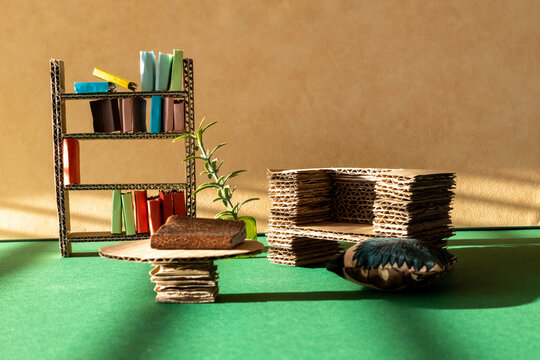 Cardboard furniture for a dollhouse interior. Cardboard sofa, bookcase and table. Room for copy.