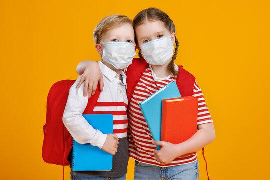 Kids in masks studying during quarantine.