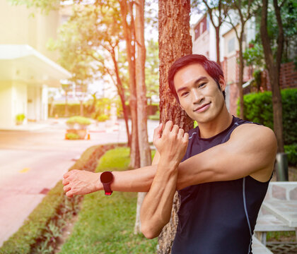 Light filter effect on man doing shoulder stretching, smiling toward in the park