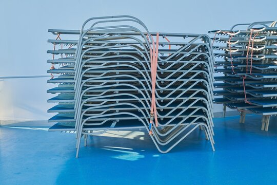 Horizontal shot of outdoor lounge chairs stacked on each other outdoors on a blue surface