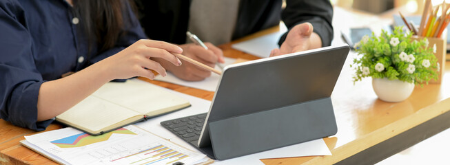 Businesswoman working with tablet, notebook and paperwork on wooden office desk