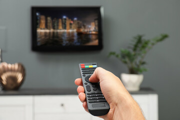 Man switching channels on TV set with remote control at home