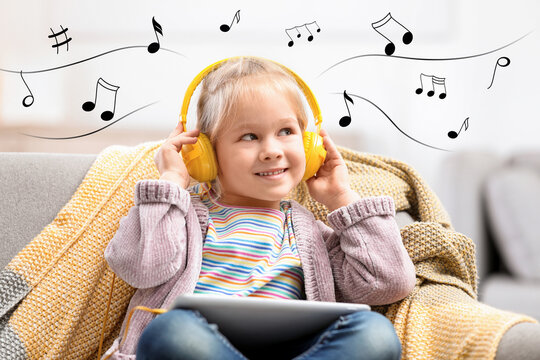 Cute little girl with headphones and tablet listening to music at home