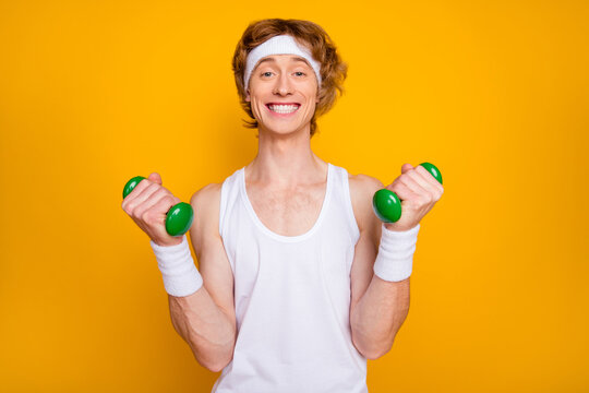 Close-up portrait of his he nice attractive funky glad cheerful cheery guy doing work out with small light dumbbell leisure isolated over bright vivid shine vibrant yellow color background
