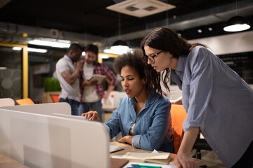 Diverse female colleagues working on project together