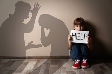 Fototapeta Sad little girl with sign HELP sitting on floor and silhouettes of arguing parents obraz