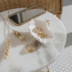 Minimal fashion composition with golden earrings in seashell on marble table with mirror and wheat stalks. Bijouterie / jewelry concept on mosaic tile background.