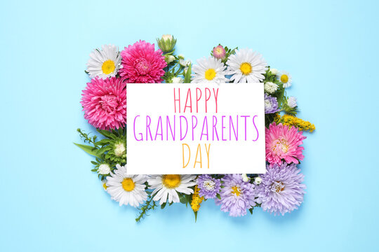 Flat lay composition with beautiful aster flowers and phrase HAPPY GRANDPARENTS DAY on light blue background