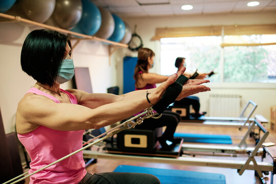 group of mature women doing excercise, Pilates and Yoga with social distancing and face mask