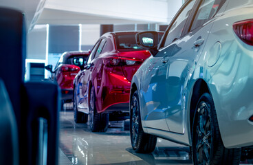 Rear view of new luxury red and white car parked in modern show room. Selective focus on white shiny car. Car dealership concept. Showroom interior. Automotive industry on coronavirus crisis concept.