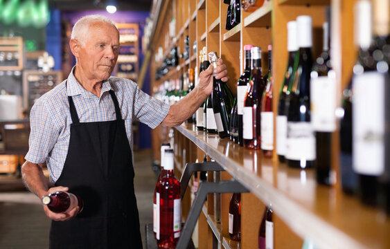 Confident elderly salesman of wine house arranging wine bottles on shelves rack