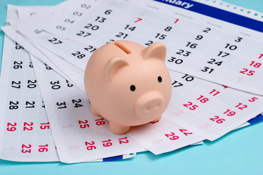 Piggy bank with a monthly calendar on a blue background. Payment of rental housing or loans.