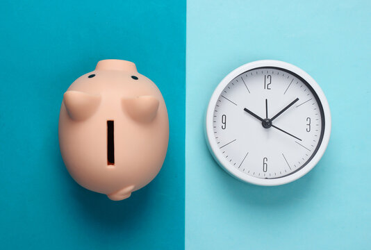 Time to invest. White clock and piggy bank on blue background. Minimalistic studio shot. Top view