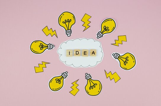 """Conceptual illustration of an m""""Idea"""" writing with yellow light bulbs and lightning icons"""