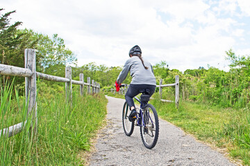 A woman rides her bicycle along a woodland path in Fairhaven, Massachusetts.
