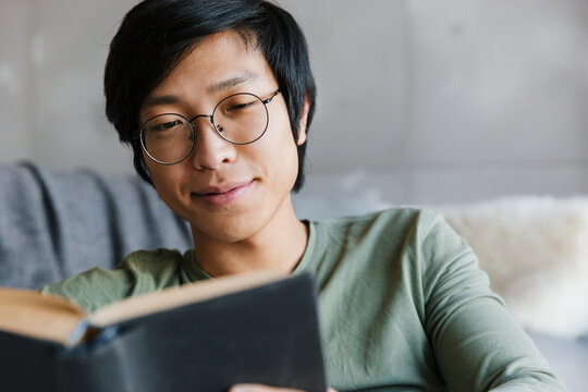 Image of young asian man wearing eyeglasses reading book in apartment