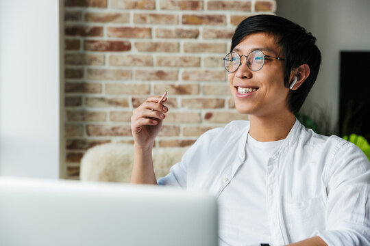 Image of young asian man wearing earphones using laptop in office