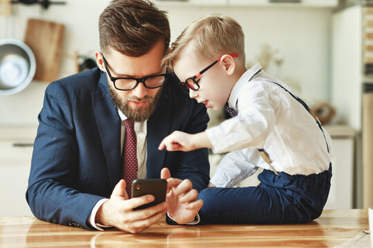 businessman father with a young schoolboy son looking at a smartphone.