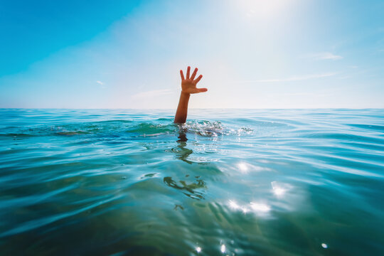 kids water safety concept- child hand see at sea, calling for help