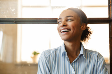 Photo of joyful african american woman smiling while leaning on wall