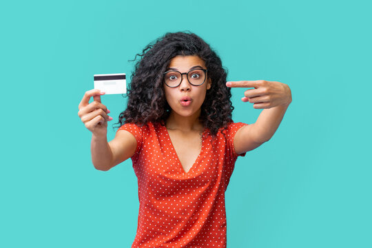 Studio portrait of happy attractive young african american woman in trendy spectacles smiling and holding credit card in hand
