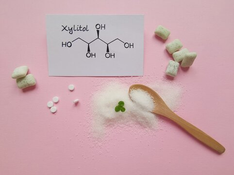 Structural chemical formula of xylitol molecule with chewing gum in the background. Xylitol is a polyalcohol (sugar alcohol), used as a food additive and sugar substitute in toothpaste and chewing gum