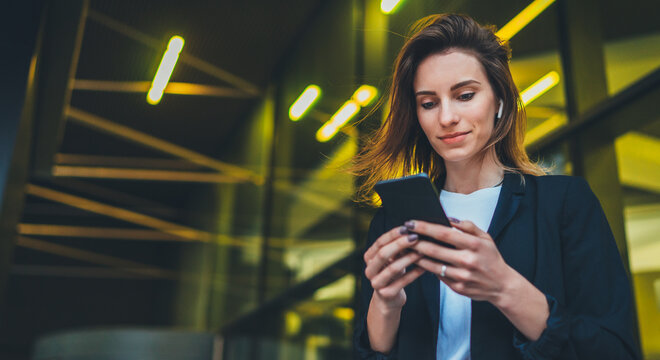 Lifestyle portrait business woman evening city and using mobile gadget, girl banker dressed in business style listening to music wireless earphones and typing text message on smartphone device