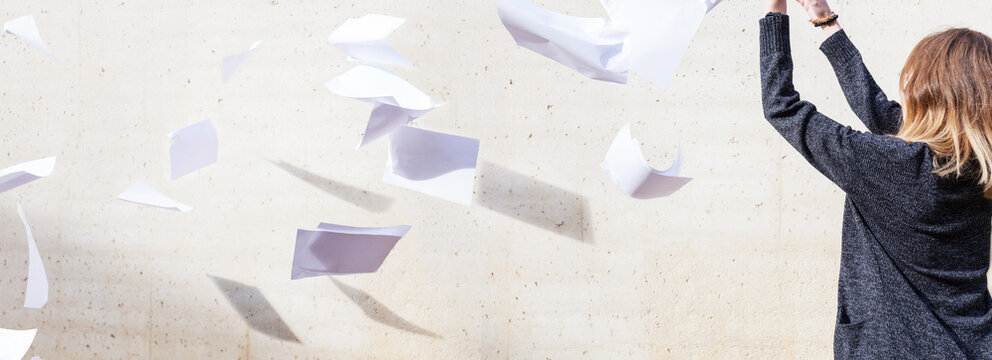 Woman throws a stack of white paper into the air tossing a wind burnout quitting giving up overwhelmed work paperless office chaos career haphazard concrete wall