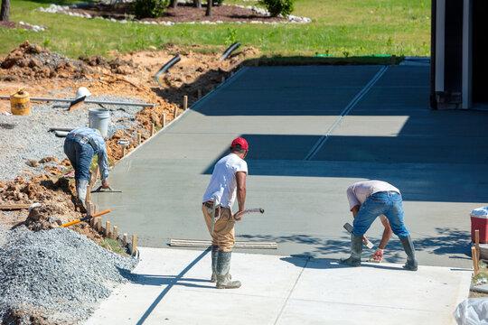 Unidentifiable Hispanic men working on a new concrete driveway