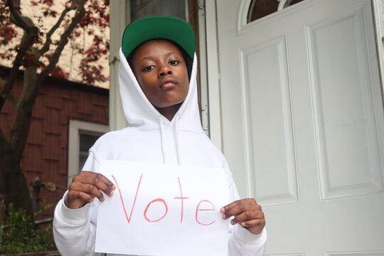 Black Kid holding white paper sign with word Vote written in red house porch background