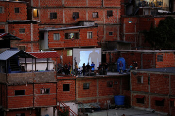 Members of Unloading zone NGO set a screen at the roof of a house in the low-income neighborhood of Petare, amid the coronavirus disease (COVID-19) outbreak in Caracas