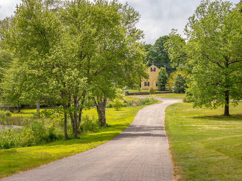 long road leading to yellow house in distance