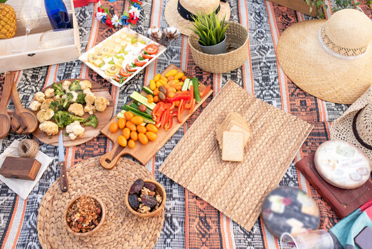 Beautiful summer picnic on the beach at sunset in zero waste style. Organic fresh fruit, cheese and vegetables on linen blanket. Eco friendly idea for weekend picnic. Top view.