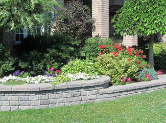 Landscape design with multiple levels and stone retaining wall for flower beds.